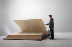 A Man Reading A Giant Book, Representing The Alcoholics Anonymous Big Book